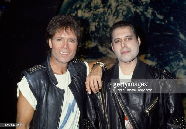 """British musicians Cliff Richard and Freddie Mercury pose together on the set of the musical """"Time"""" at the Dominion Theatre in London, England circa..."""