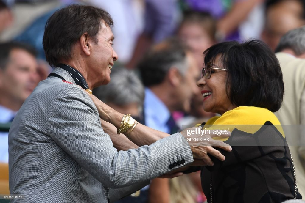 TOPSHOT - British musicians Cliff Richard and Shirley Bassey embrace on centre court before watching US player Serena Williams play Germany's Julia Goerges during their women's singles semi-final match on the tenth day of the 2018 Wimbledon Championships at The All England Lawn Tennis Club in Wimbledon, southwest London, on July 12, 2018. (Photo by Glyn KIRK / AFP) / RESTRICTED