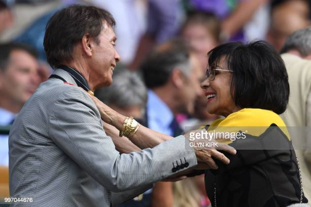 TOPSHOT British musicians Cliff Richard and Shirley Bassey embrace on centre court before watching US player Serena Williams play Germany's Julia...