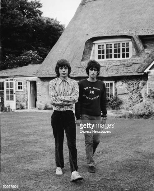 British musicians Mich Jagger and Keith Richards of the rock group The Rolling Stones walk in the garden of Redlands, Richards' Sussex house, after...