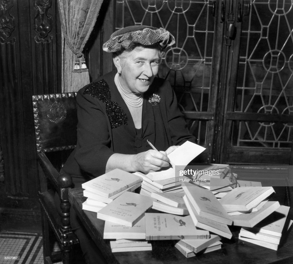 British mystery author Agatha Christie (1890-1976) autographing French editions of her books.