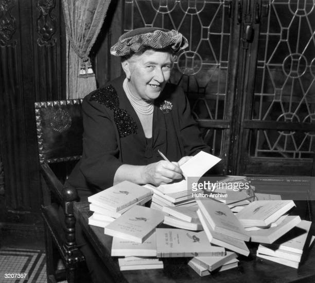 British mystery author Agatha Christie autographing French editions of her books, circa 1950.
