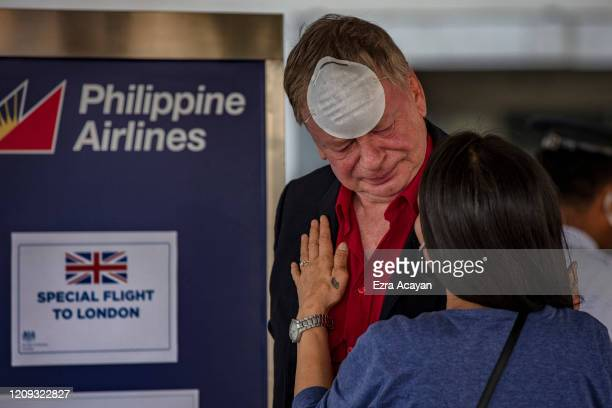 British national shares a moment with his partner upon arriving at Ninoy Aquino International Airport to get on a special flight to London on April 7...