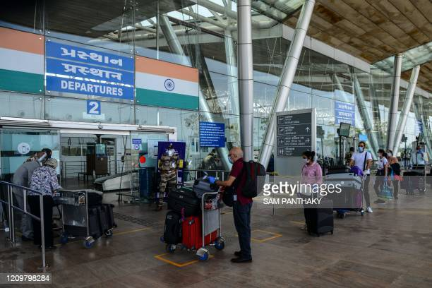 British nationals queue up outside a departures terminal before boarding a special British Airways flight during Indian governmentimposed nationwide...