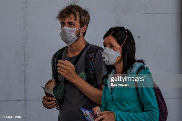 British nationals wearing facemasks arrive at Ninoy Aquino International Airport to get on a special flight to London on April 7 2020 in Manila...