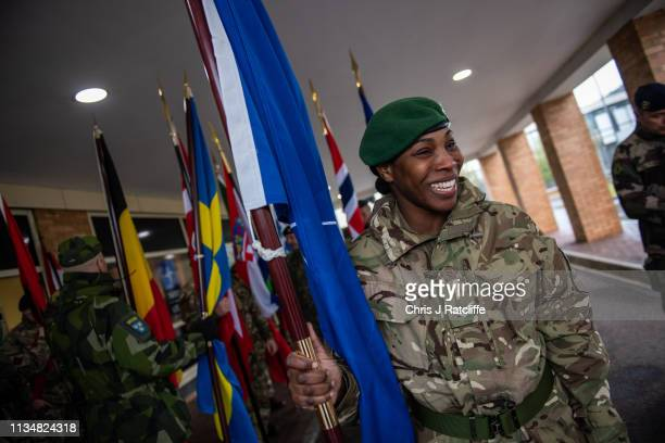 British NATO military personnel holds the NATO flag before the start of the NATO commemorative parade at Imjin Barracks on April 4 2019 in Gloucester...