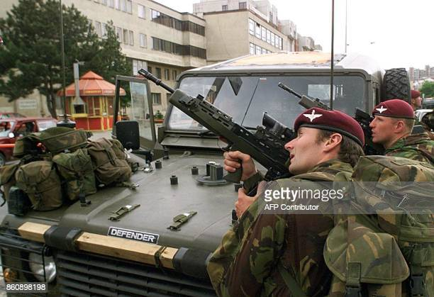 British NATO soldiers secure the site where an unidentified sniper injured the driver of a stolen car in the center of Pristina 17 June 1999 / AFP...