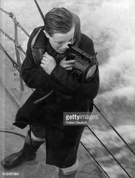 A British Naval signalman with an Aldis Lamp