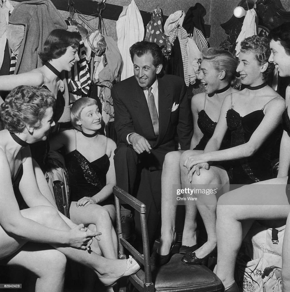 British nightclub owner and publisher Paul Raymond (1925 - 2008) chats with some of the women in his employ, September 1956.