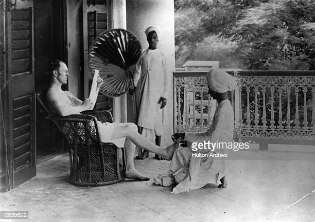 A British officer in India receives a pedicure from an Indian servant