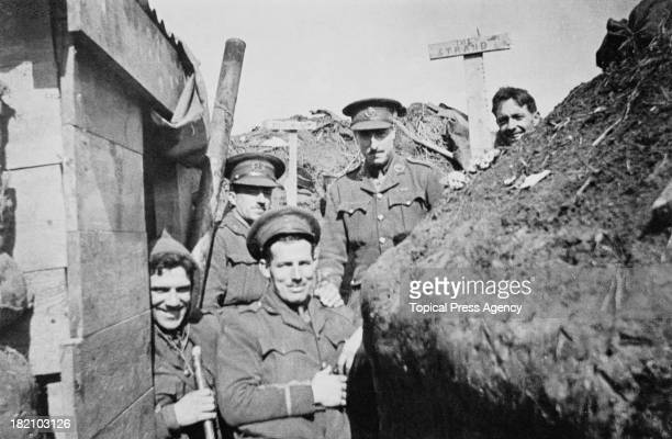 British officers in a trench probably in Belgium during World War I circa 1915 The two signs behind them read 'Piccadilly' and 'The Strand'