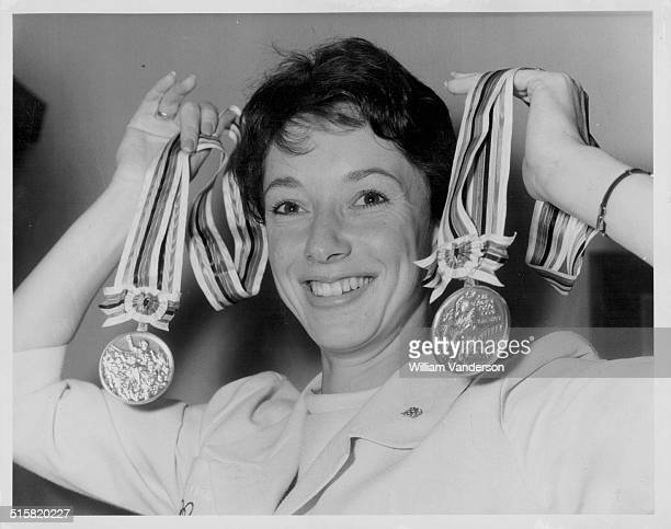 British Olympic athlete Ann Packer posing with her gold and silver medals at London Airport on her way to meet the Queen at Buckingham Palace London...