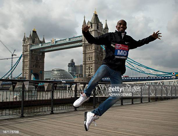 British Olympic double gold medallist Mo Farah jumps in front of Tower Bridge during a photo call the day after the 2013 London Marathon in central...