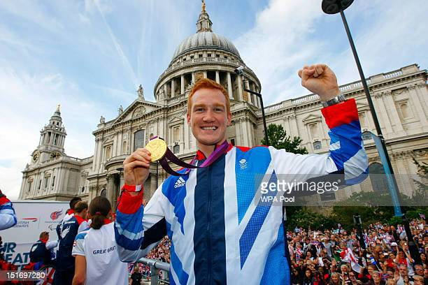 British Olympic gold medal winning athlete Greg Rutherford holds his long jump gold medal as he takes part in the parade passing St Paul's Cathedral...