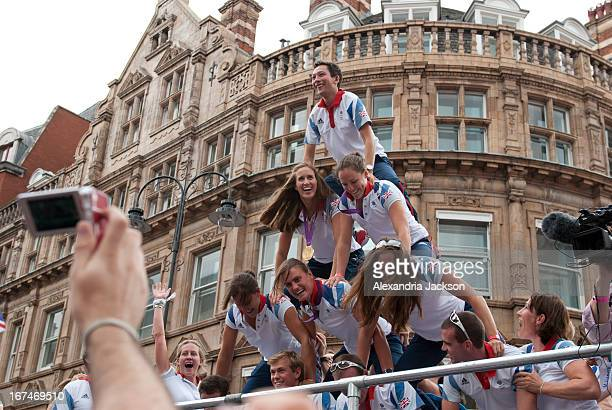 CONTENT] British Olympic team form a human pyramid during the Olympic parade in London to celebrate the end of the Olympics