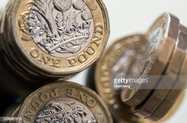 British one pound coins stand stacked in this arranged photograph in Danbury UK on Monday March 23 2020 The pound rose boosted by broad dollar...