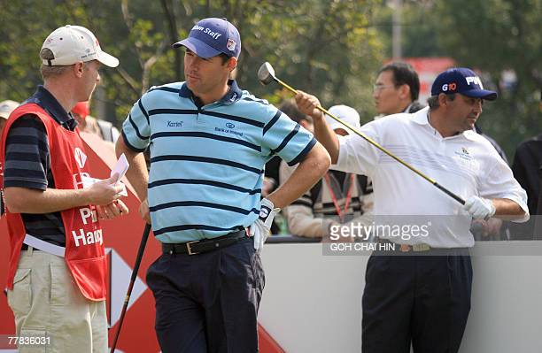 British Open Champion Padraig Harrington of Ireland chats with his caddy as US Open Champion Angel Cabrera of Argentina waits for his turn to tee off...