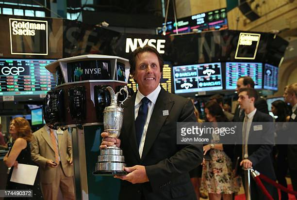 British Open golf champion Phil Mickelson holds the Claret Jug on the floor of the New York Stock exchange on July 26 2013 in New York City Mickelson...