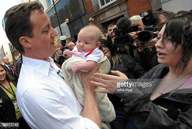 British opposition Conservative party leader David Cameron holds a baby while campaigning in Tamworth central England on April 20 2010 The General...