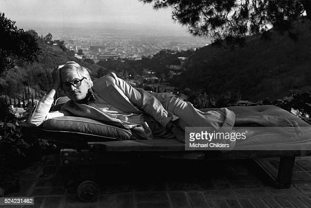 British painter draughtsman printmaker stage designer and photographer David Hockney lounging by the pool in Rising Glen circa 1978