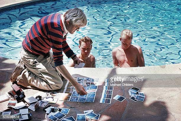 British painter draughtsman printmaker stage designer and photographer David Hockney poolside in Los Angeles with polaroids of David Stoltz Ian...