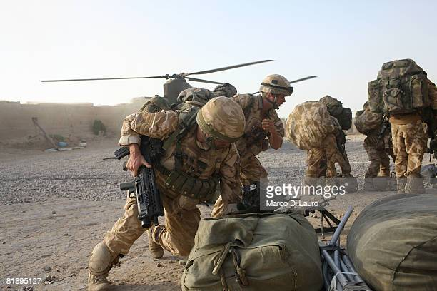 British Paratrooper from the 2nd BattalionThe Parachute Regiment take cover as they wait for a Chinook helicopter to land to evacuate six British...