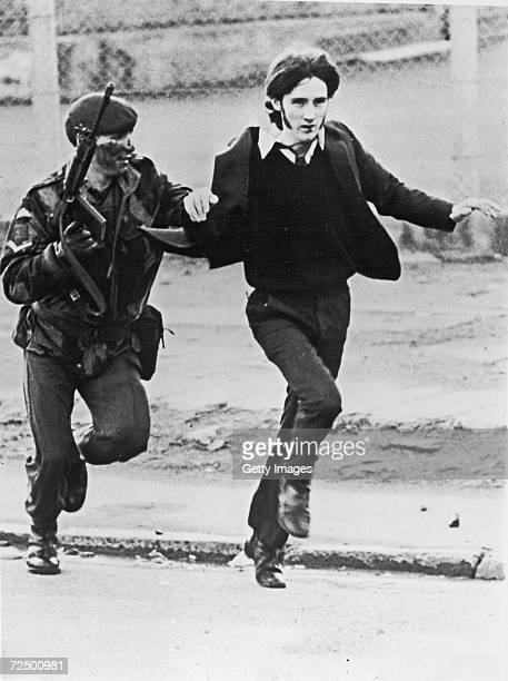 British paratrooper takes a captured youth from the crowd on Bloody Sunday when British paratroopers opened fire on a civil rights march killing 14...