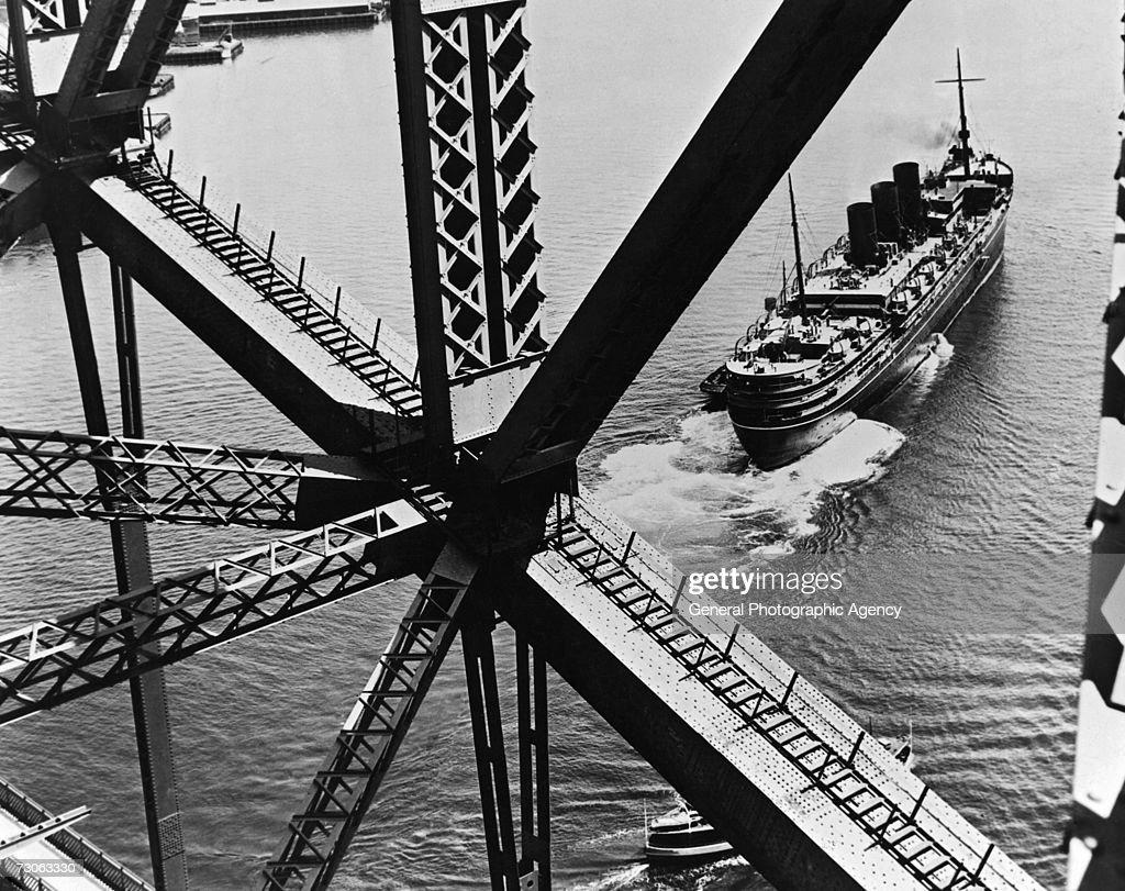 A British passenger liner passing under Sydney Harbour Bridge, Australia, circa 1935.