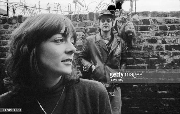 British performance artist and musician Cosey Fanni Tutti holding a small dog and British singersongwriter and musician Genesis POrridge of Throbbing...