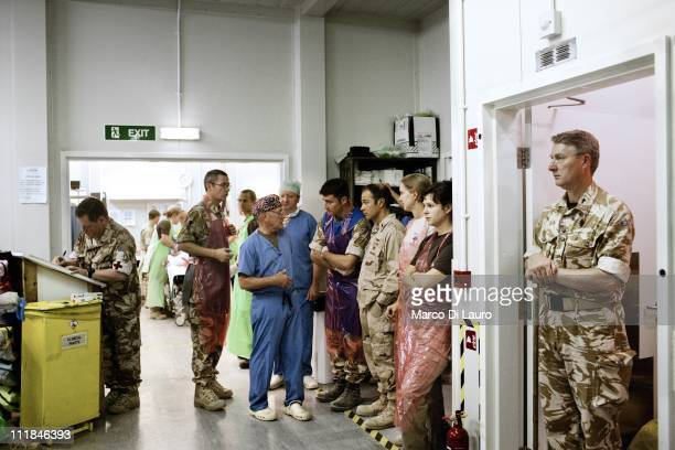 British personnel of the United Kingdom Med Group and American medic personnel and the hospital Chaplain stand watching an Afghan National Army...