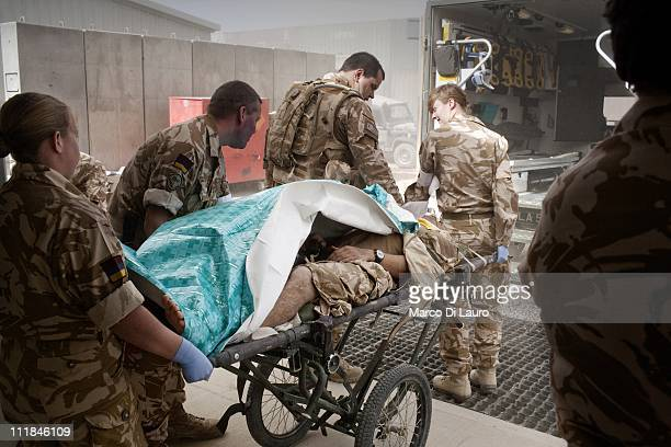 British personnel of the United Kingdom Med Group carry a stretcher with a wounded British soldier out of the ambulance into the Camp Bastion...