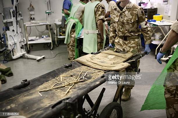 British personnel of the United Kingdom Med Group carry an empty stretcher with just some dirt and a body armour after thry deliver a wounded British...
