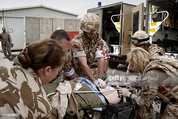 British personnel of the United Kingdom Med Group perform a cardio-pulmonary resuscitation to a wounded British soldier as they carry him out of the...