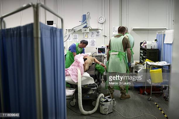 British personnel of the United Kingdom Med Group treat a wounded British soldier in the Emergency Department at the Camp Bastion Hospital on...