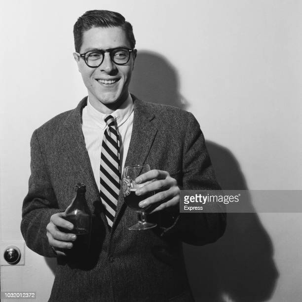 British philanthropist and book collector John Paul Getty Jr smiles while holding a bottle of beer and a pint glass UK 11th April 1963