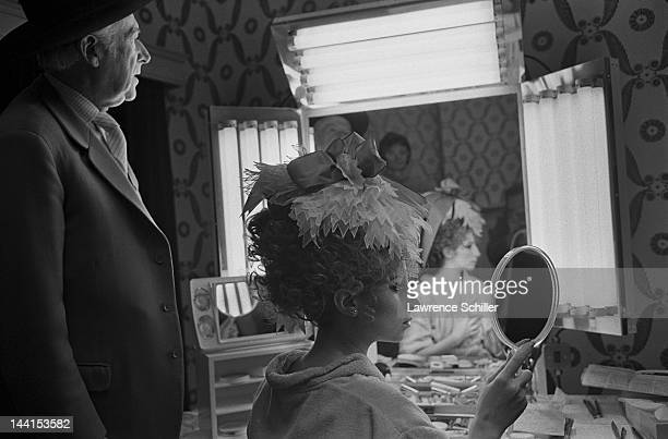 British photographer and fashion designer Cecil Beaton watches as American singer and actress Barbra Streisand as she looks into a mirror in the...
