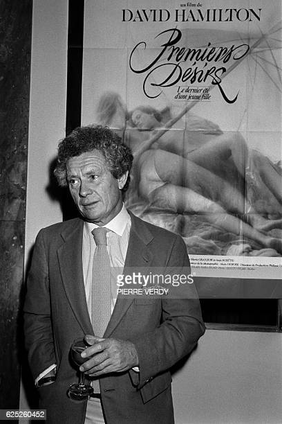 British photographer and film director David Hamilton poses on November 19 1983 in front of the poster of his erotic film First Desires during a sale...