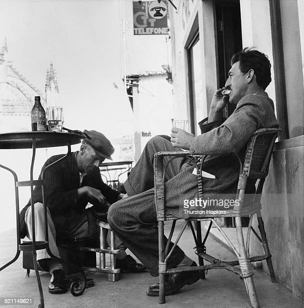 British photographer and photojournalist Thurston Hopkins engages the services of a shoeshine during a voyage through Portugal May 1954 Original...