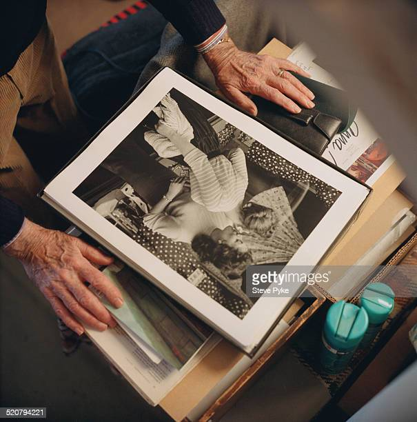 British photographer and photojournalist Thurston Hopkins looking at his 1956 photograph of model Andria Loran in Seaford East Sussex UK 10th...