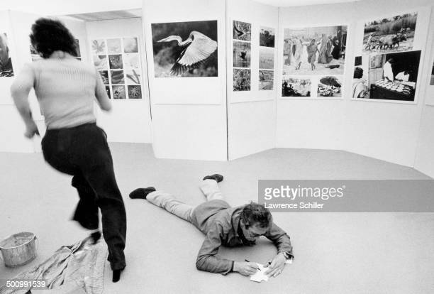 British photographer Antony ArmstrongJones 1st Earl of Snowdon lies on the floor and makes notes as he sets up an exhibition 1974