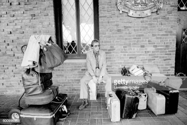 British photographer Antony ArmstrongJones 1st Earl of Snowdon sits on a bench under the Coat of Arms of the Netherlands and waits with his luggage...