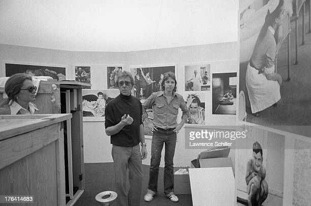 British photographer Antony ArmstrongJones 1st Earl of Snowdon speaks with Beverly Chamberlain and another as he sets up an exhibition of his work...