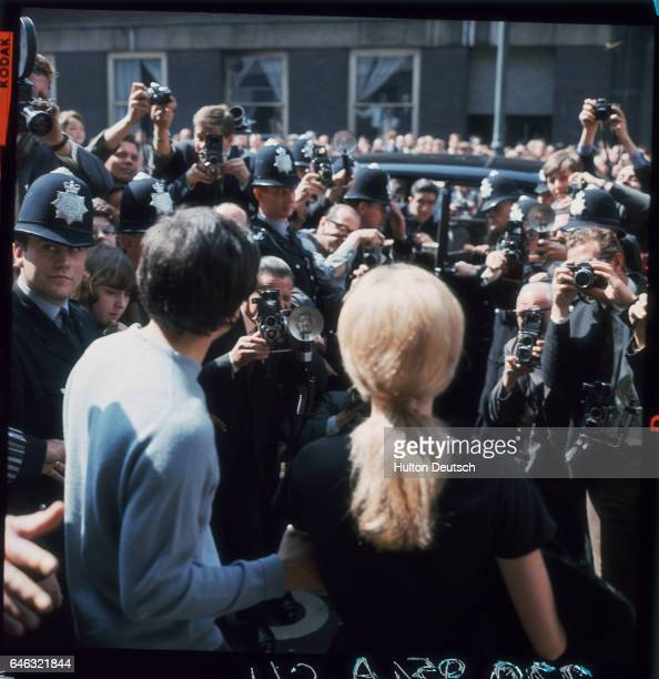 British photographer David Bailey and actress Catherine Deneuve are surrounded by press photographers as they leave St Pancras after their wedding