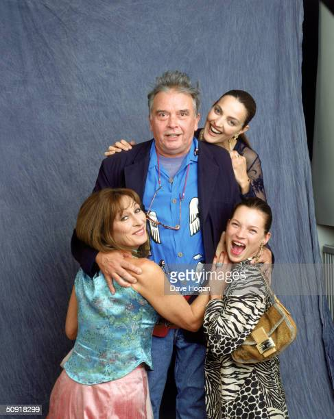 British photographer David Bailey succombs to the attentions of his wife Catherine, supermodel Kate Moss and actress Anjelica Huston, circa 2000.