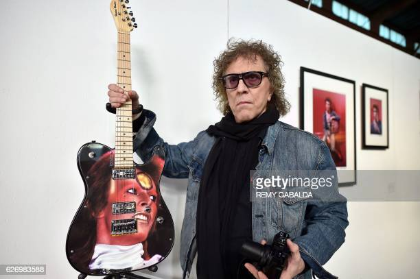 British photographer Mick Rock poses with a guitar picturing British singer David Bowie on December 1 2016 in his exhibition Life on Mars on David...