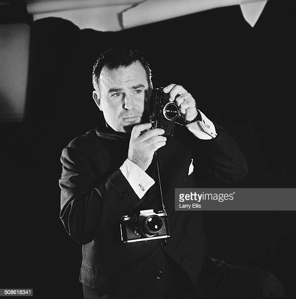 British photojournalist, Terry Fincher poses with a camera, 1964.