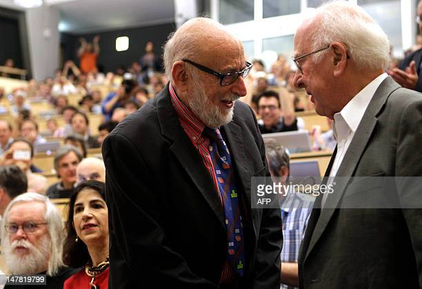 British physicist Peter Higgs shakes hands with Belgium physicist Francois Englert on July 4 2012 before the opening of a seminar to deliver the...