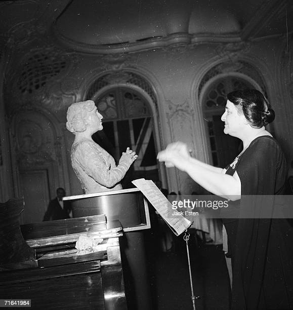 British pianist Dame Myra Hess conducts Haydn's 'Toy Symphony' of toy musical instruments at the Savoy Hotel London 14th July 1945 On the left is a...