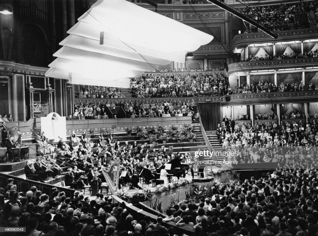 British pianist Harriet Cohen (1895 - 1967) in concert with conductor Malcolm Sargent (1895 - 1967) at the Royal Albert Hall in London, 25th July 1950. Cohen, who lost the use of her right hand in an accident in 1948, is performing the 'Concertante for Orchestra with Piano (Left Hand)' written especially for her by composer Arnold Bax.
