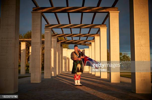 British Piper Steve Black plays at sunrise to mark the 77th anniversary of D-Day at the British Normandy Memorial on June 06, 2021 in Ver-sur-Mer...